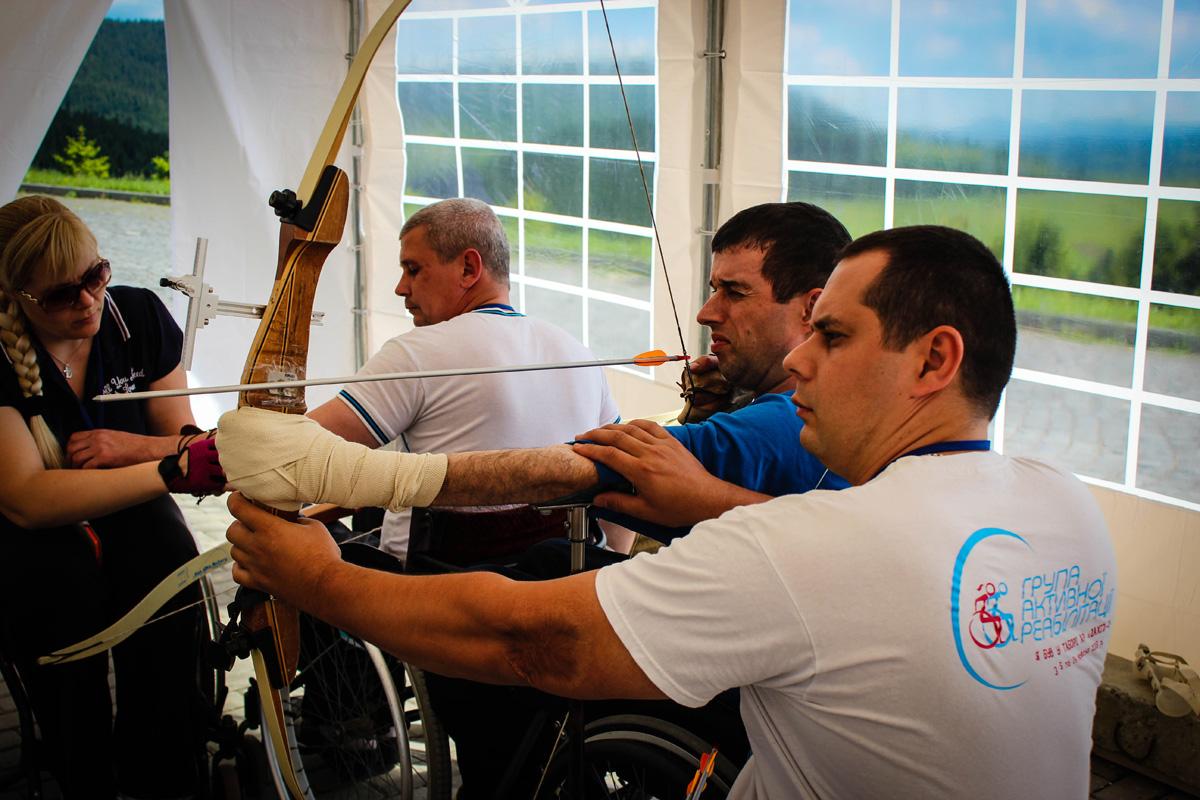 Інструктор зі стрільби з лука Андрій Чеберяк допомагає учаснику з шийною травмою